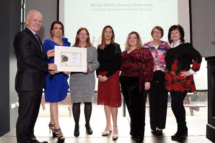 Maria Donnellan, the multi-disciplinary team, and her mother accepting an award at the Community Healthcare West Staff Recognition Awards ceremony from Tony Canavan, Chief Officer,  Community Healthcare West.
